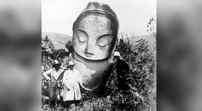 Beberapa orang berdiri di depan sebuah patung megalitik pada 1930-an (Tropenmuseum)